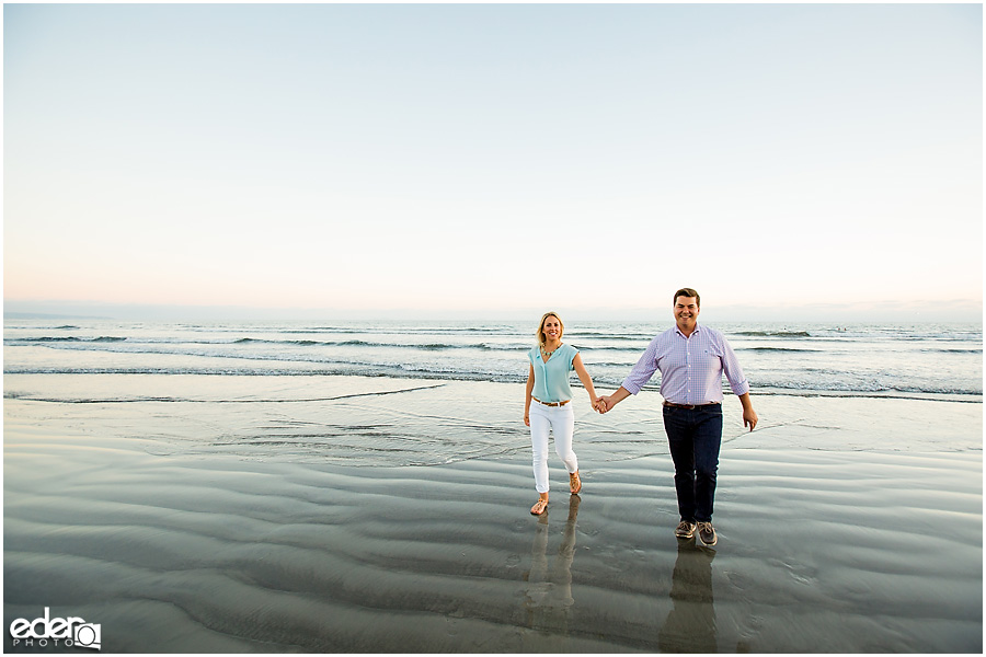 Couple walking on beach during engagement session in Coronado, CA.