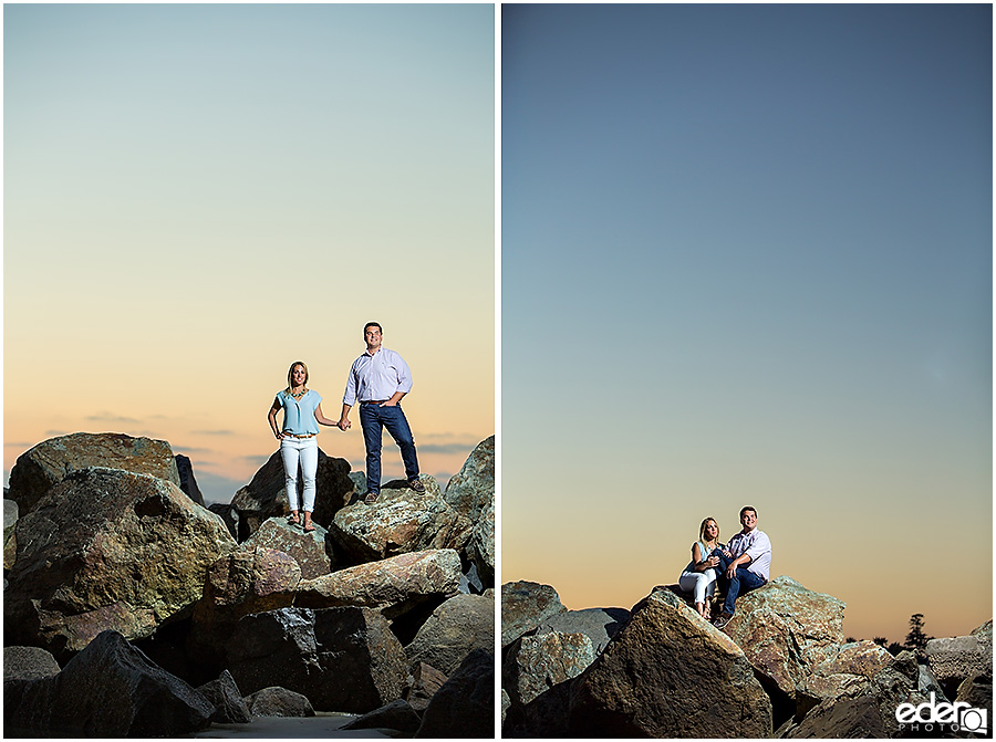 Couple on rocks in front of the Hotel Del Coronado during engagement session.