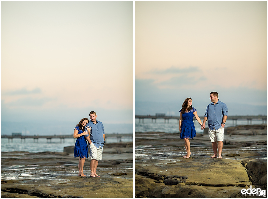 Standing on rocks San Diego Sunset Cliffs engagement session.