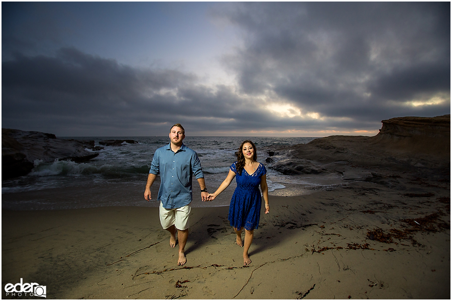 Walking on the sand during San Diego Sunset Cliffs engagement session.