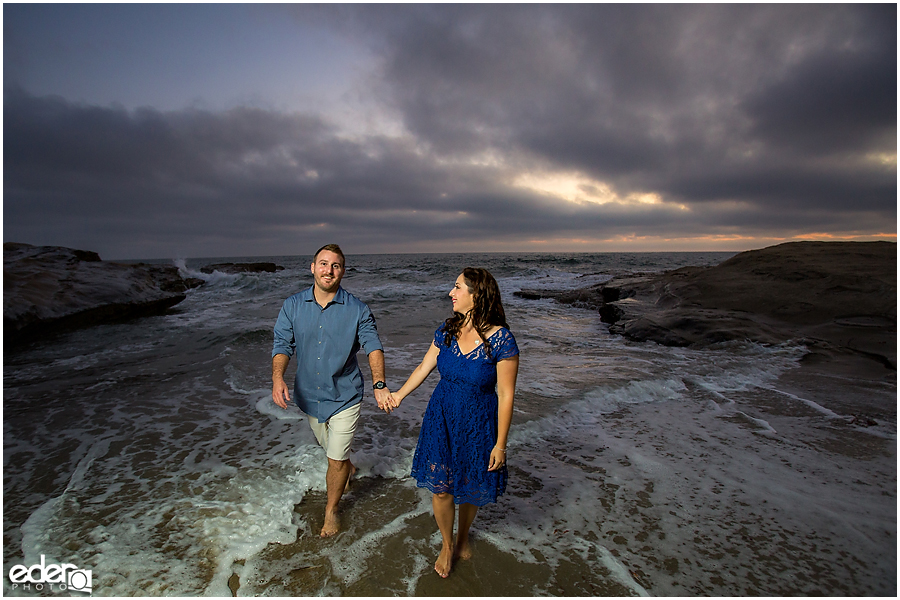 Walking in water during San Diego Sunset Cliffs engagement session.