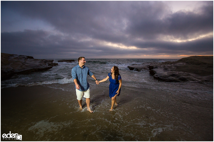 Walking in water San Diego Sunset Cliffs engagement session.