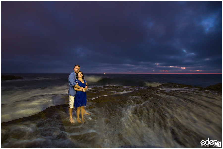 Standing still as water rushes by during an engagement session.