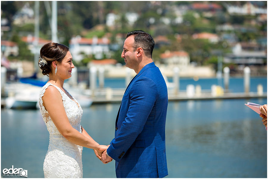 Couple with water in the background during beach elopement at the Kona Kai Resort in San Diego, CA.