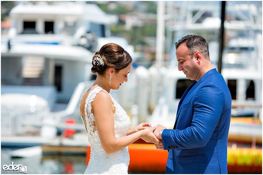 Ring exchange during beach elopement at the Kona Kai Resort in San Diego, CA.