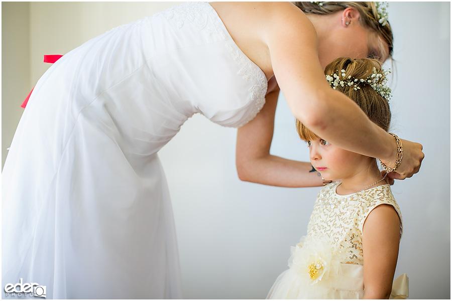 Flower girl receiving jewelry.
