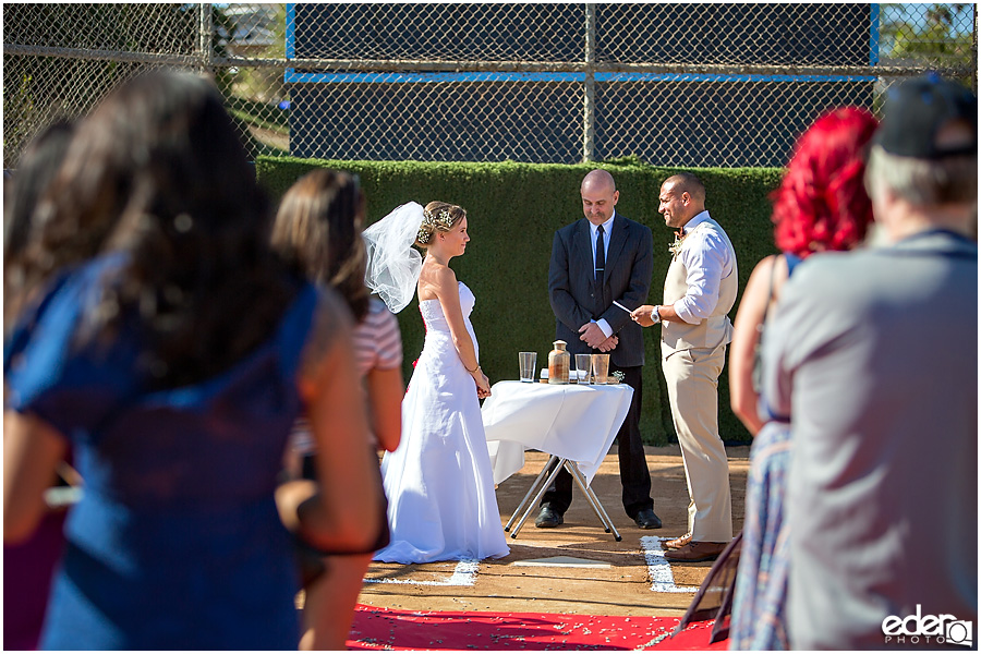 Exchanging vows during baseball themed wedding ceremony.