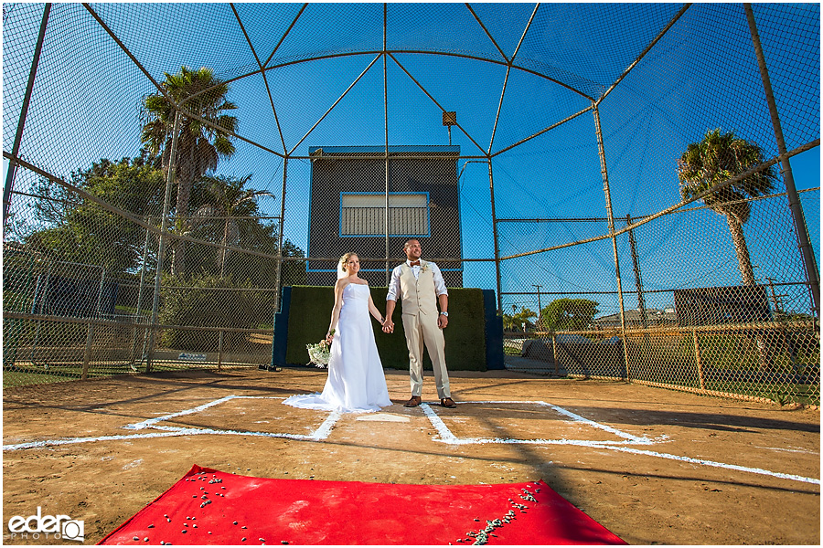 Bride and groom at home plate after baseball themed wedding ceremony.