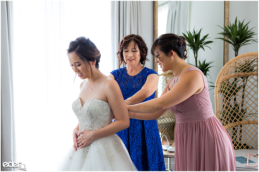 Wedding at The US Grant - photo of bride putting dress on.